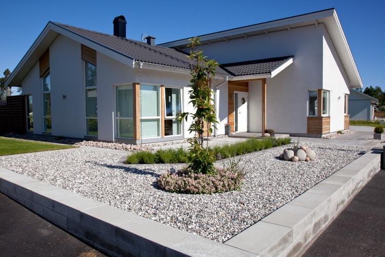 Ett vit hus med dekorsten på framgården